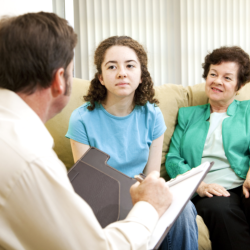 Teenage girl and her mother meeting with a psychologist.